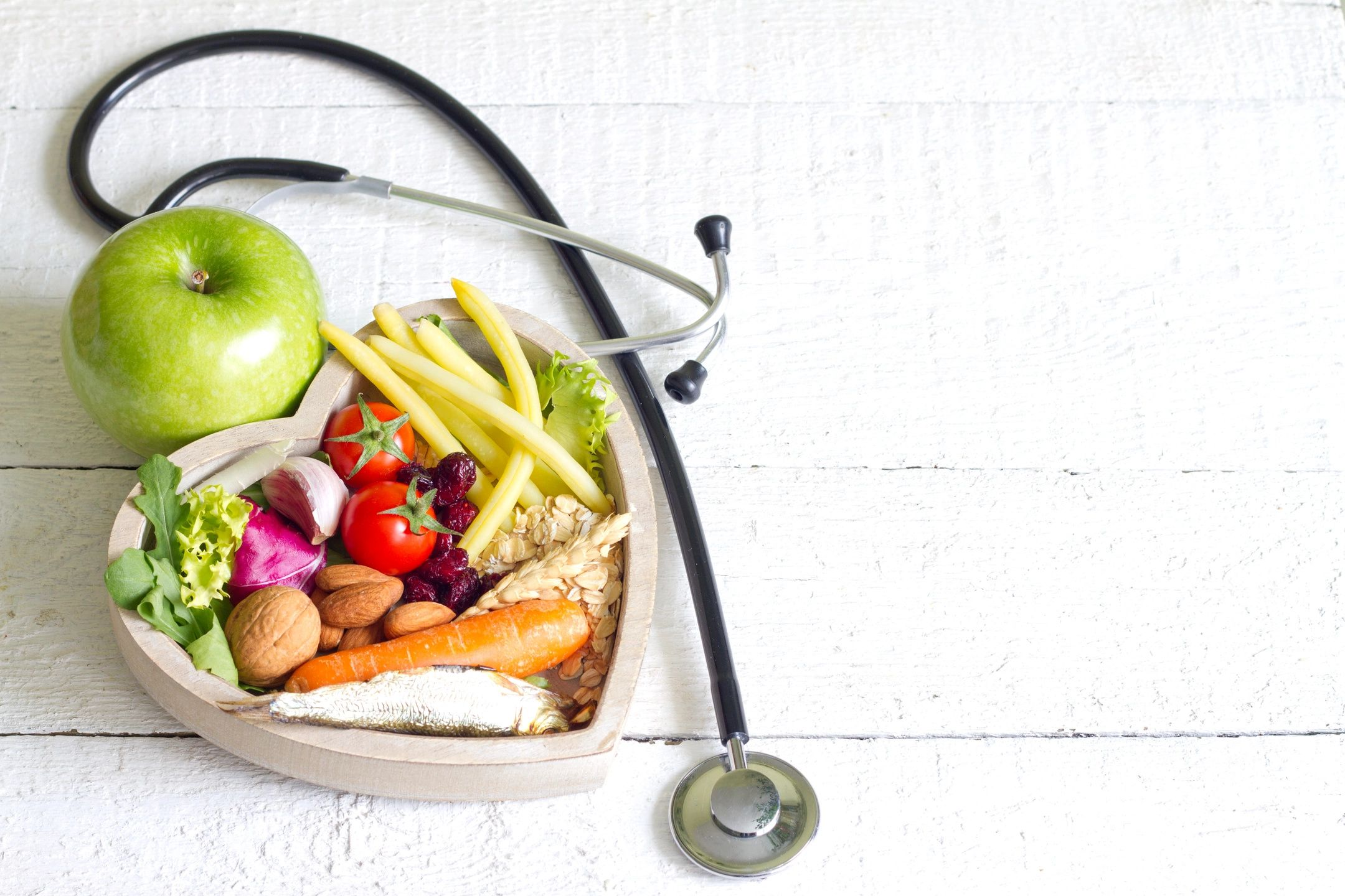 Naturopathic medicine portrayed in this picture of vegetables in a heart shaped box, and a stethoscope