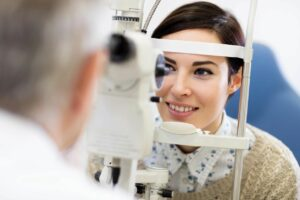 male eye doctor, doctor of optometry assessing a female patient's eyes using a medical device.